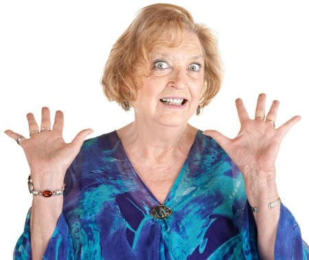 aghast: Frightened European senior female with hands up Stock Photo