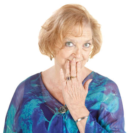 embarrassed: Blushing Caucasian grandmother with hand over mouth