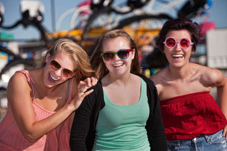 native american girl: Group of three laughing teenage girls at an amusement park