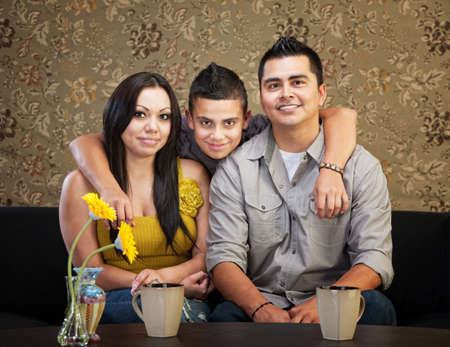 Young smiling Latino family sitting indoors together Stock Photo