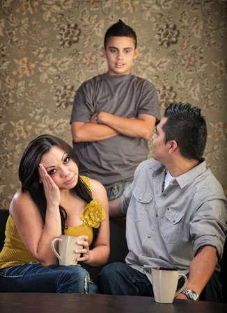 children talking: Teenager talking to annoyed parents sitting Stock Photo