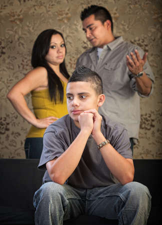 trio: Young Latino boy in blank stare with concerned parents behind him Stock Photo