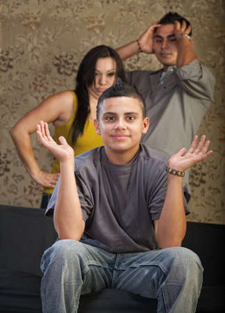 Teenage male with hands up and annoyed adults