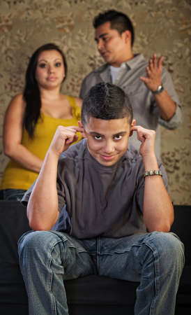 Grinning Hispanic teenager plugging his ears with frustrated parents photo