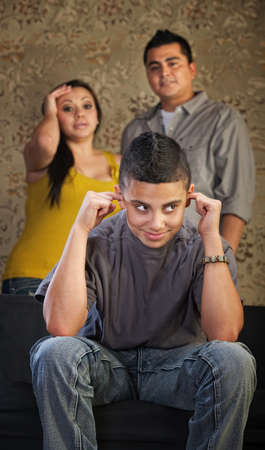 Frustrated parents and child with ears plugged photo