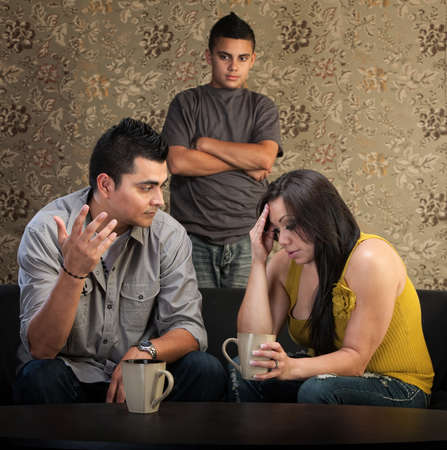 Worried Native American couple with upset son indoors Stock Photo