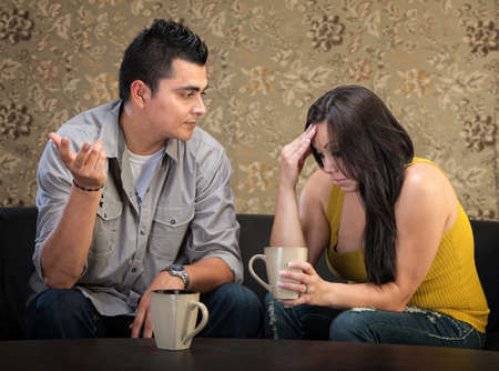 concerned: Depressed young Hispanic woman in conversation with man