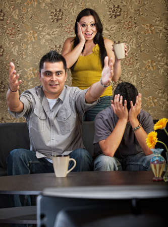 Excited man and woman with distraught son watching television photo