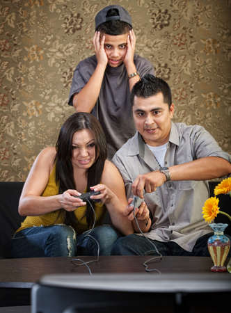 Embarrassed Hispanic teenager behind parents playing video games photo