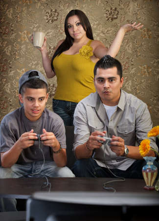 Hopeless mother behind father and son playing video games