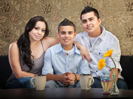 Smiling young Latino family of three sitting together photo