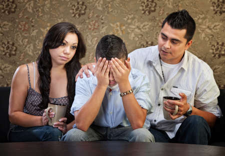 Sympathetic Latino parents with depressed male teenager photo