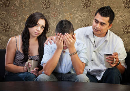 Latino parents comforting sad male teenager with hands in face photo