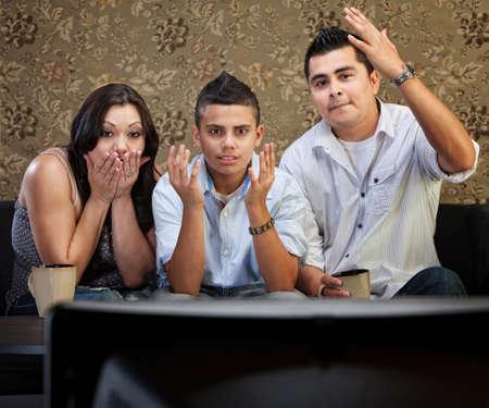 suspens: Choqu� famille de trois enfants de regarder la t�l�vision avec les mains en l'air Banque d'images