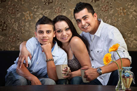 Happy Latino family hugging each other indoors photo