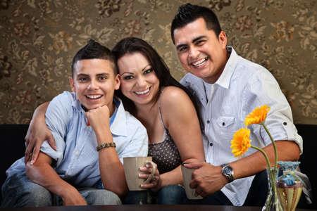 niños latinos: Familia feliz abrazando Latino de tres en un sofá Foto de archivo