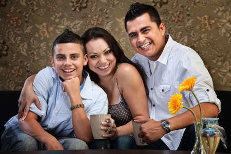 Happy Latino family of three embracing on a sofa photo