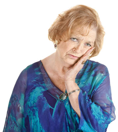 toothache: Tired older woman in blue with hand on cheek Stock Photo