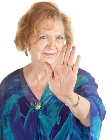 Senior Europese vrouw in blauw met hand omhoog Stockfoto