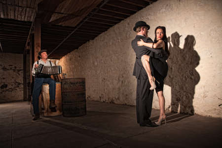 Mature tango dancers under spotlight with bandoneon player