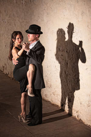 Beautiful female tango dancer with leg up next to partner photo