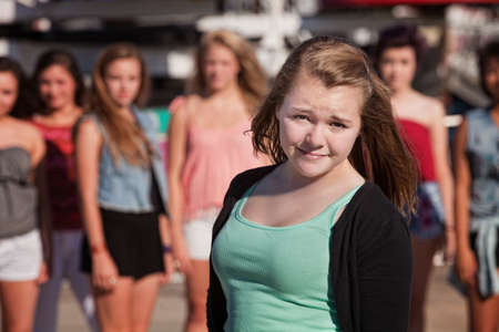 Young cute teen female in front of group of girls photo