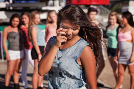 intimidated: Shy teenage Filipino girl looking down with friends nearby