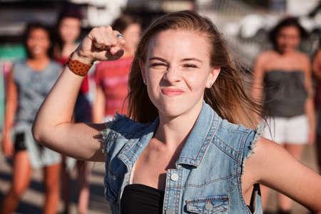 mujeres peleando: Angry chica joven en la chaqueta de mezclilla sacude su puño Foto de archivo