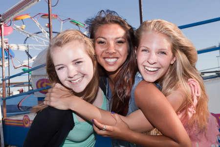adolescentes riendo: Grupo de tres amigas adolescentes asi�ticos y blancos en un carnaval Foto de archivo