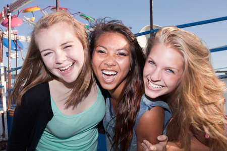 giggling: Three Asian and white teenage friends laughing together