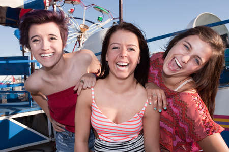 Group of three pretty teenage girlfriends at an amusement park photo