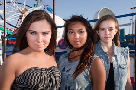 bff: Trio of serious teenage girls at an amusement park Stock Photo