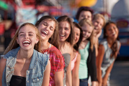 bff: Group of eight girls in a row laughing Stock Photo