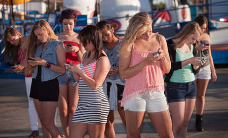 Eight teenage girls distracted with their phones at carnival