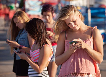 Four female teenagers using their phones outside photo