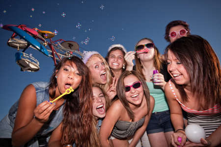 Diverse group of teen girls at carnival blowing bubbles photo