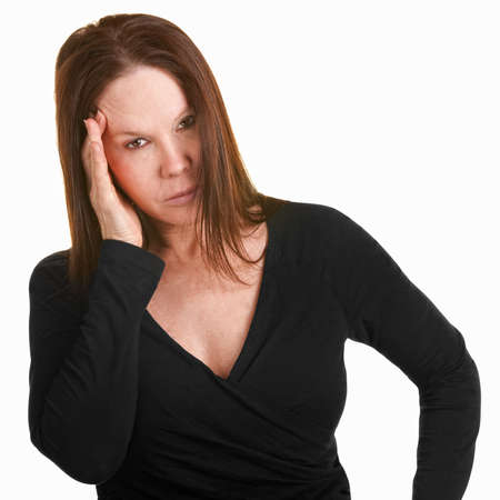 frowning: Unhappy European woman in black with hand on head Stock Photo