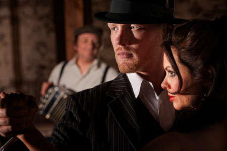 1920s style Tango dancers looking ahead with bandoneon player in background photo