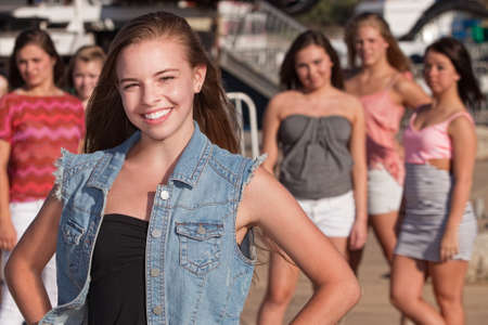 Confident young Caucasian girl in front of jealous friends Stock Photo - 15433164