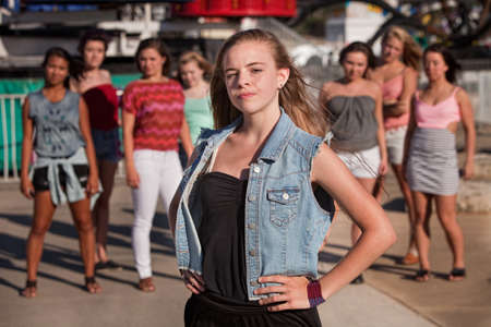 Young blond girl with a confident attitude in front of friends