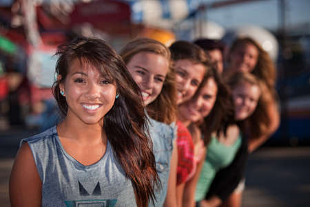Mixed row of eight smiling girls outside together photo