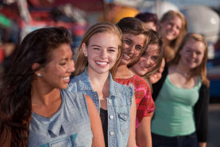 pretty teen girl: Smiling teenage girls standing behind each other in line