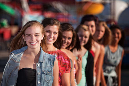 bff: Group of eight girlfriends in a row smiling