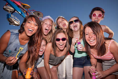 Group of happy girls with bubbles at amusement park photo
