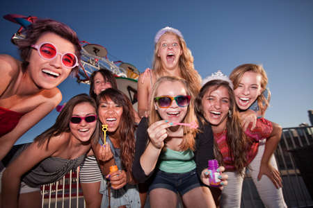 bff: Laughing teenage girls blowing bubbles at an amusement park