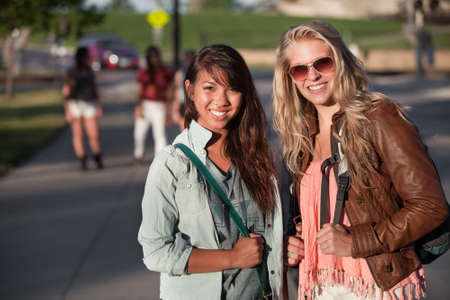 Two smiling teenage female students on school campus photo