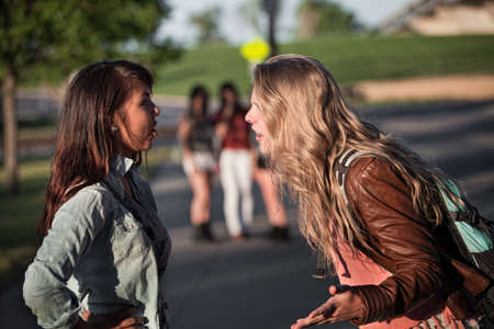 aggressive people: Two serious teenage female students arguing outside Stock Photo