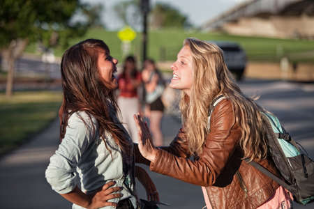 Two excited female teenage students talking outside photo