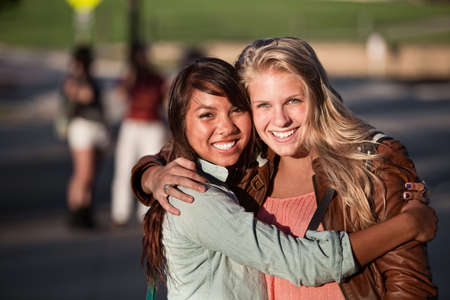 friends hugging: Two hugging female students hugging each other outdoors