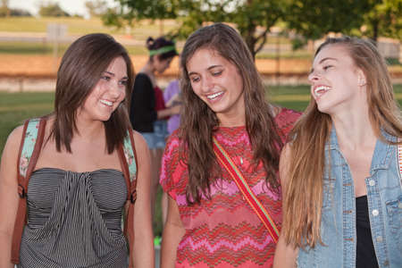 Group of three cute teenage students laughing and talking photo